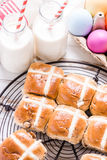 Hot cross bun on tray with Easter vibrant eggs and milk. Stock Photos