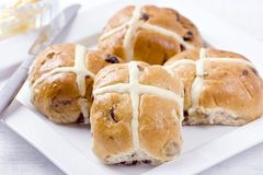 Hot Cross Buns. Sticky hot cross buns with raisins on white plate with butter and knife Royalty Free Stock Images
