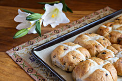 Hot Cross Buns on Baking Tray - Lilies. Hot cross buns on a baking pan with white Easter Lily flowers in the background Stock Image