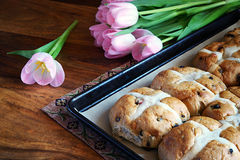 Hot Cross Buns on Baking Tray - Tulips. Hot cross buns on a baking pan with fresh cut tulips in the background Stock Images