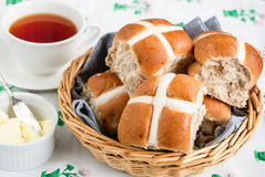 Hot Cross Buns. In a basket with a knife and butter and a cup of tea Royalty Free Stock Photos