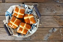 Hot Cross Buns in a basket, over rustic wood Royalty Free Stock Photos