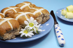 Hot Cross buns with butter curls on blue background - close-up. Traditional Australian and English Easter Good Friday meal, Hot Cross Buns, on blue polka dot Royalty Free Stock Images