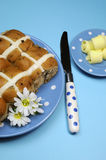 Hot Cross buns with butter curls on blue background - vertical aerial. Royalty Free Stock Image