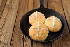 Hot cross buns in cast iron skillet on wooden background Royalty Free Stock Photography