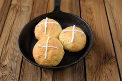 Hot cross buns in cast iron skillet on wooden background Royalty Free Stock Photo