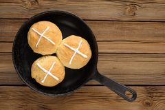 Hot cross buns in cast iron skillet on wooden background Royalty Free Stock Images