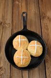Hot cross buns in cast iron skillet on wooden background Royalty Free Stock Image
