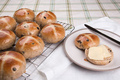 Hot cross buns  on a cooling rack  with one on a plate cut and buttered Stock Photo