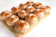 Hot cross buns  on a cooling rack set on a wooden board Royalty Free Stock Photography