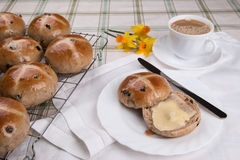 Hot cross buns  on  cooling tray with one cut and buttered Royalty Free Stock Photos