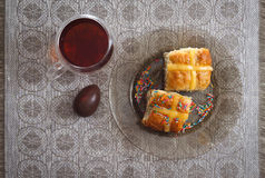 Hot cross buns, cup of tea and chocolate eggs on easter table Stock Photography