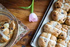 Hot Cross Buns Easter Breakfast. Hot cross buns on a baking pan and a breakfast place setting featuring a buttered bun ready for eating Stock Photo
