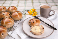 Hot cross buns glazed and baked on a cooling tray with one cut and buttered Stock Photos