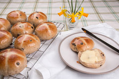 Hot cross buns glazed and baked on a cooling tray with one cut and buttered Royalty Free Stock Images