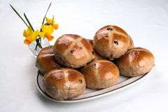 Hot cross buns heaped on an oval plate with daffodils. Hot cross buns heaped on a white oval plate with vase of daffodils  on a white background Royalty Free Stock Photos