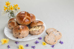 Hot cross buns on an oval plate, currant biscuits, with a vase of flowers. Hot cross buns on an oval plate one sliced ready to eat , cuttant biscuits in front Stock Photo
