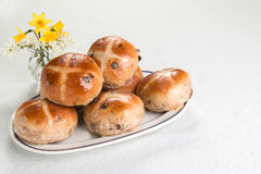 Hot cross buns  on an oval plate with spring flowers. Hot cross buns traditional British Easter fare on an oval plate with spring flowers at the back Stock Photos