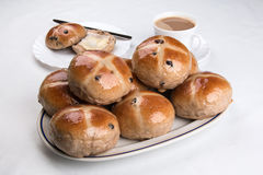 Hot cross buns  on an oval plate with spring flowers Stock Photo