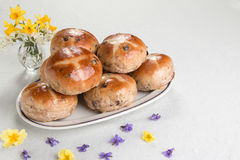 Hot cross buns on an oval plate, with a vase of flowers. Hot cross buns on an oval plate with primrose and violet flowers, and vase of daffodils,  horizontal Royalty Free Stock Photos