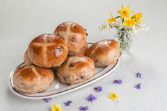 Hot cross buns on an oval plate, with a vase of flowers. Hot cross buns on an oval plate with a vase of spring flowers and flower heads scattered Stock Photo
