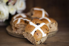 Hot Cross Buns Still Life with Flowers. Hot cross buns with flowers behind.  Easter treats on old board with timber background. Focus on front bun. Shallow depth Royalty Free Stock Image