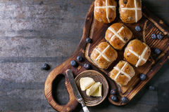 Hot cross buns. On wooden cutting board served with butter, knife, fresh blueberries and jug of cream over old texture metal background. Top view, space. Easter Royalty Free Stock Image