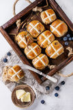 Hot cross buns. In wooden tray served with butter, fresh blueberries, knife and jug of cream on textile napkin over white texture concrete background. Top view Stock Image