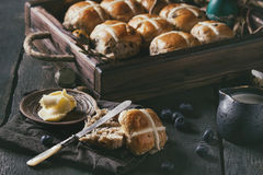 Hot cross buns. In wooden tray served with butter, knife, blueberries, easter eggs, birch branch, jug of cream on textile napkin over old texture wood royalty free stock images