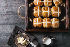 Hot cross buns. In wooden tray served with butter, knife and jug of cream on textile napkin over old texture metal background. Top view, space. Easter baking Royalty Free Stock Image