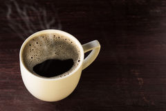 Hot cup of brewed black coffee on wooden table Royalty Free Stock Photos