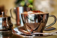 Cappuccino with Chritmas Bokeh. A hot cup of Cappuccino in a silver cup with pots of milk and sugar in selective focus with Christmas fairy lights bokeh in the Stock Photo