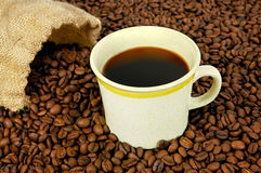 Hot cup of coffee. Coffee cup with burlap sack of beans Stock Photography
