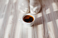 Hot cup of coffee ahead of winter socks. Closeup of hot cup of coffee ahead of winter socks Royalty Free Stock Image