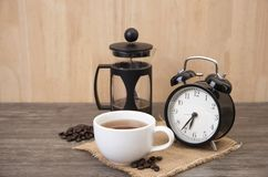 Hot cup of coffee and alarm clock on wood. stock image