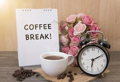 Hot cup of coffee and alarm clock on wood table with rose flower royalty free stock images
