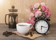 Hot cup of coffee and alarm clock on wood table with rose flower royalty free stock photos