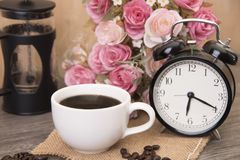 Hot cup of coffee and alarm clock on wood table with rose royalty free stock images