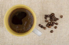 Hot cup of coffee and beans on burlap Stock Photo