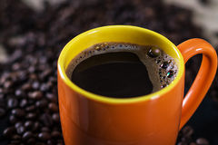 Hot cup of coffee. Cup of hot coffee on coffee beans, close-up Stock Photos