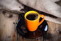 Hot cup of coffee. Cup of hot coffee with coffee beans on wooden background, close-up Stock Image