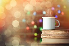 Hot cup of coffee and books with fairy lights Stock Photography