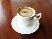 Hot cup of coffee cappuccino. Decorated with cinnamon in white creamy on wooden table blackground Stock Images