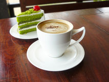 Hot cup of coffee cappuccino and layer green tea cake Stock Photos