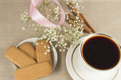 A hot Cup of coffee, cinammon cookies with sprigs of gypsophilla and pink ribbon Royalty Free Stock Photo