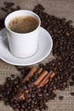 Hot cup of coffee with cinnamon and coffee grains. Cup of coffee with coffee grains and cinnamon Stock Photo