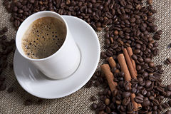 Hot cup of coffee with cinnamon and coffee grains. Cup of coffee with cinnamon and coffee grains Stock Photo