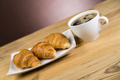 Hot cup of coffee with croissants in the restaurant Stock Photos