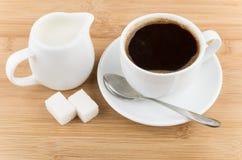 Hot cup of coffee, jug milk, spoon and sugar Royalty Free Stock Photos