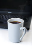 Hot cup of coffee with a laptop in the background Royalty Free Stock Images